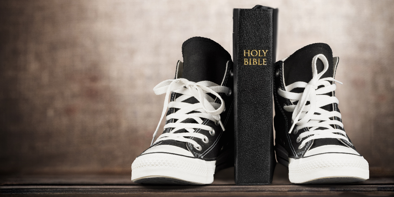 bible sandwiched between two baseball boots
