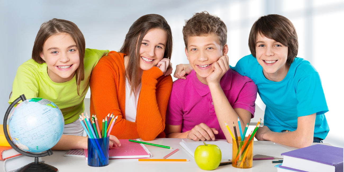four youths leaning on a desk and smiling