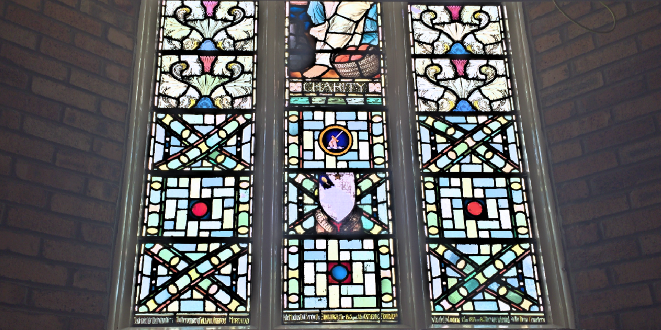 a stained-glass window in the church wall